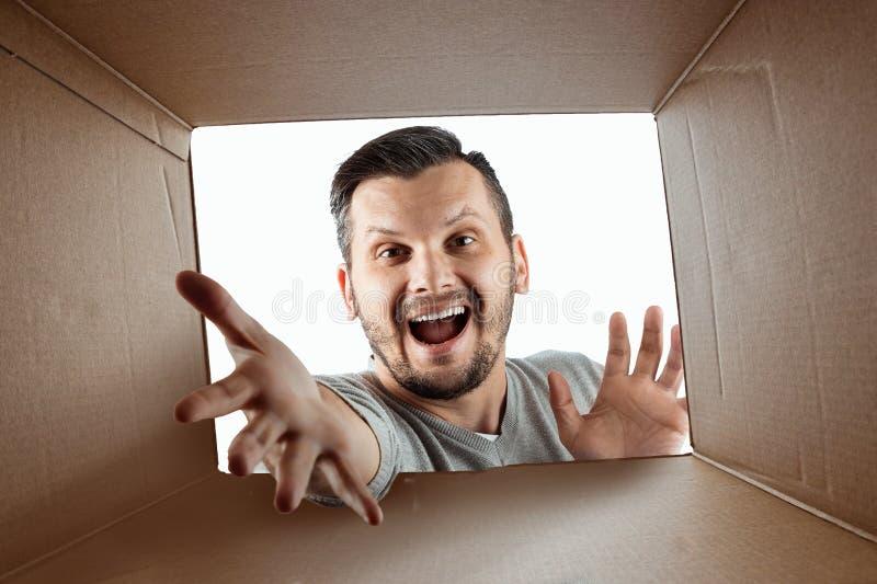 Unboxing öppnar idérik bakgrund, den glade mannen asken och blickarna i överraskning Packen, leverans, överraskning, gåva arkivbilder