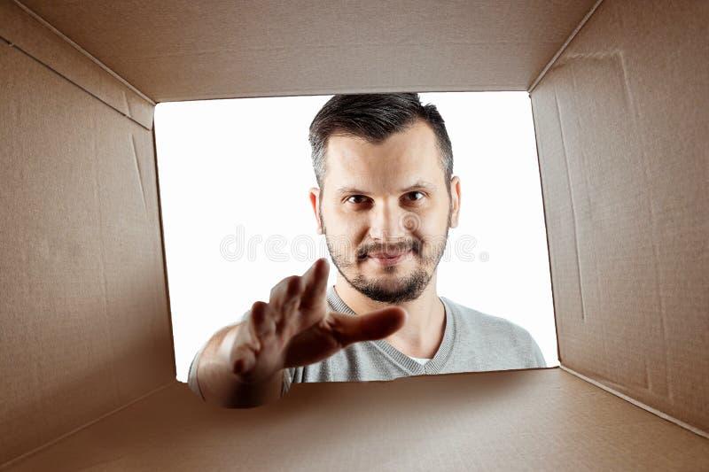 Unboxing öppnar ser idérik bakgrund, en man asken och inom Packen, leverans, överraskning, gåva, livsstil arkivbilder