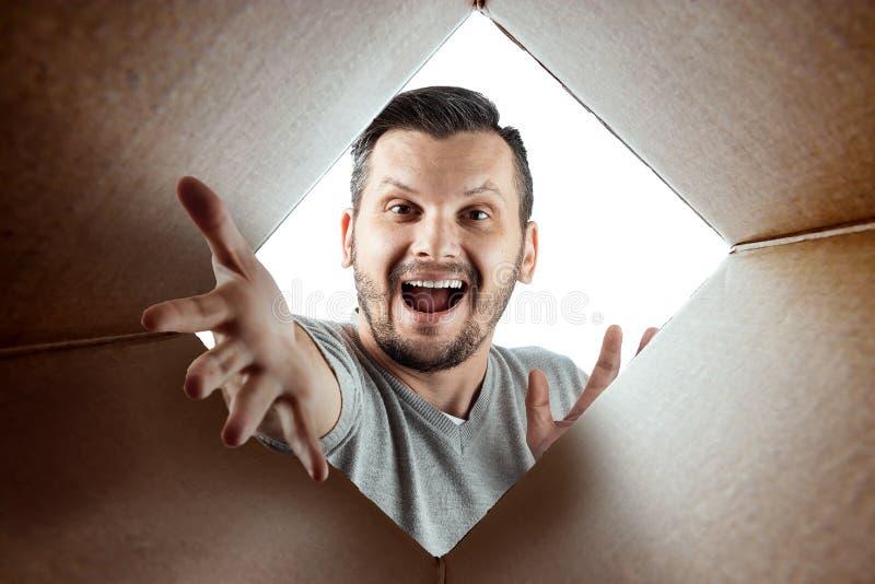 Unboxing, el fondo creativo, hombre alegre abre la caja y las miradas en sorpresa El paquete, entrega, sorpresa, regalo foto de archivo