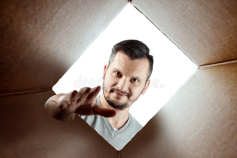 Unboxing, le fond créatif, un homme ouvre la boîte et regarde à l'intérieur Le paquet, la livraison, surprise, cadeau, mode de vi images libres de droits