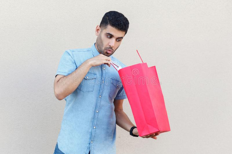 Unboxing and looking inside of bag. Portrait of handsome young bearded man in blue shirt standing, holding red shopping bag,. Looking inside. indoor studio shot royalty free stock image