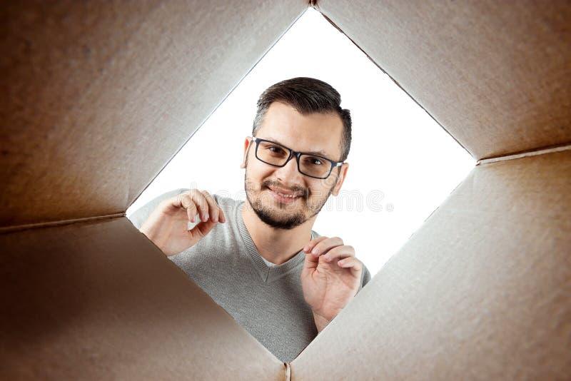 Unboxing, o fundo criativo, um homem abre a caixa e olha para dentro O pacote, entrega, surpresa, presente, estilo de vida imagem de stock