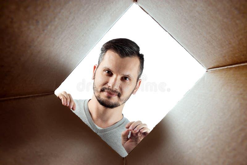 Unboxing, o fundo criativo, um homem abre a caixa e olha para dentro O pacote, entrega, surpresa, presente, estilo de vida imagens de stock