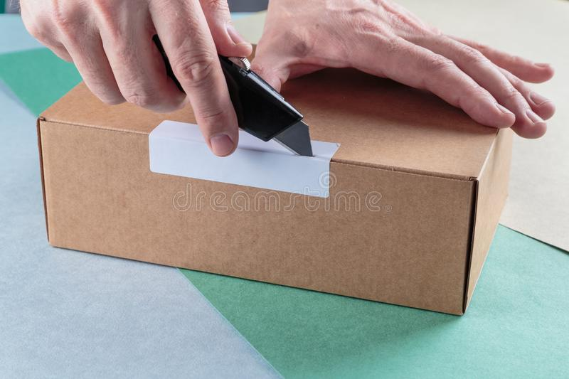 Unboxing the parcels Packed. In a cardboard box with a utility knife stock photography