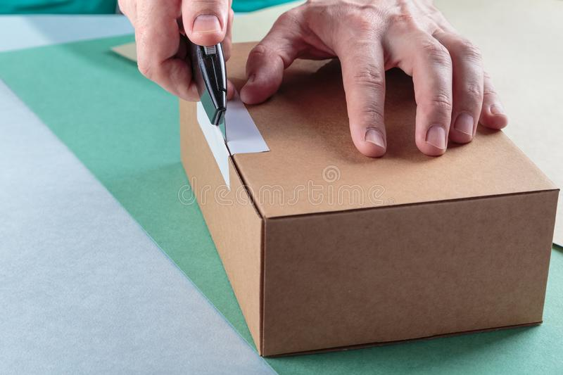 Unboxing the parcels Packed. In a cardboard box with a utility knife stock image