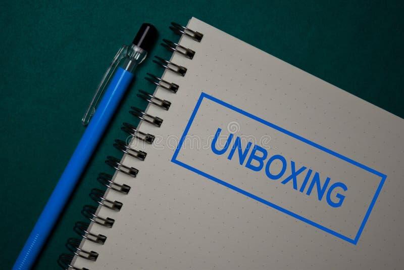 Unboxing schrijf op een boek dat op groene achtergrond wordt geïsoleerd stock fotografie