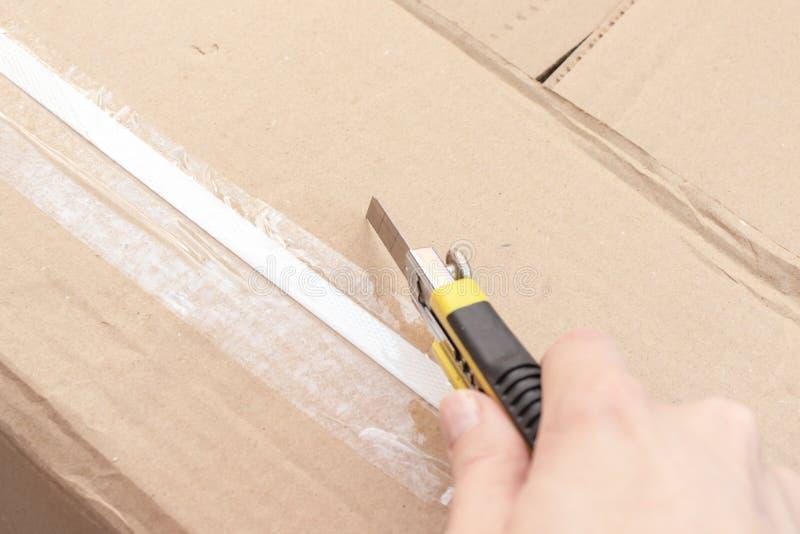 Unboxing una scatola di cartone con nuova mobilia con il coltello dell'ufficio o della costruzione - muovendosi verso la nuova ca fotografia stock