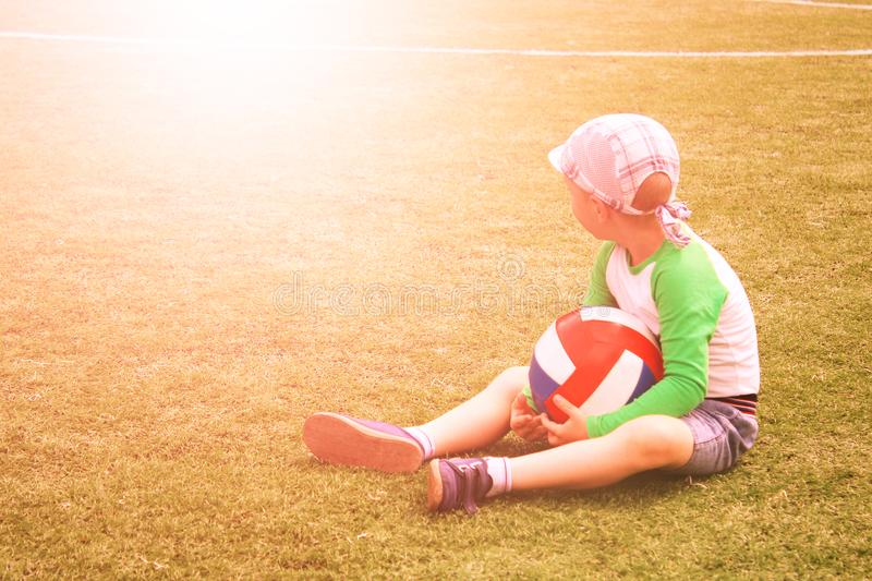 Uncertain baby boy sitting next to soccer ball at football field. Football training concept. Toned stock photography