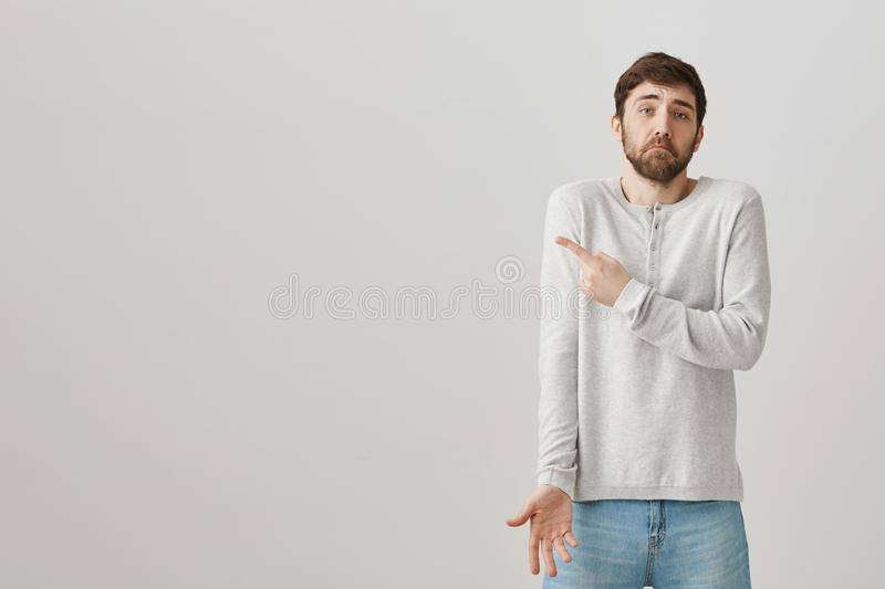 Uncertain charming caucasian guy with beard and moustache shrugging and pointing left while being questioned and upset. Standing over gray background. I am not royalty free stock images