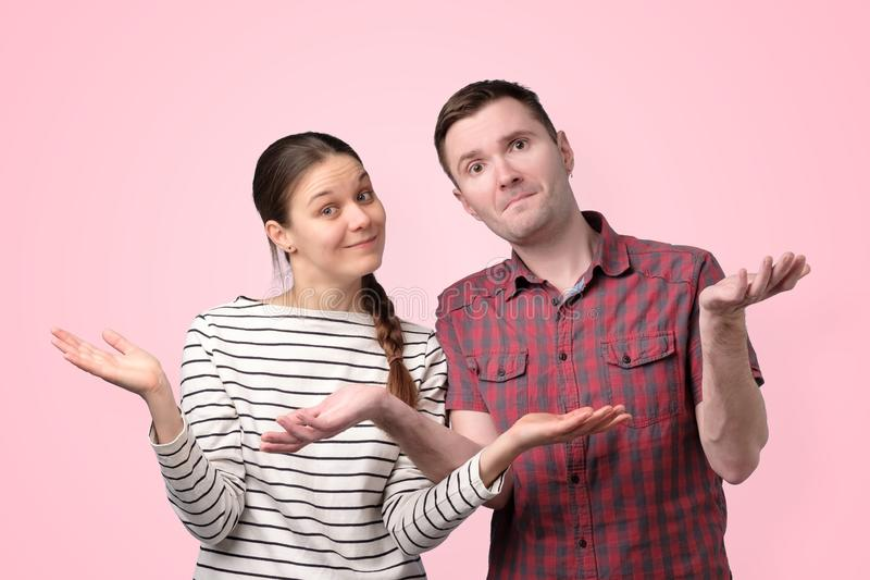 Uncertain couple shrugging shoulders  over pink background stock photos