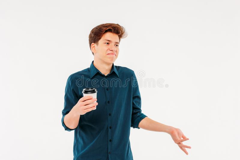 Uncertain doubting young man student with paper Cup of coffee stock photo