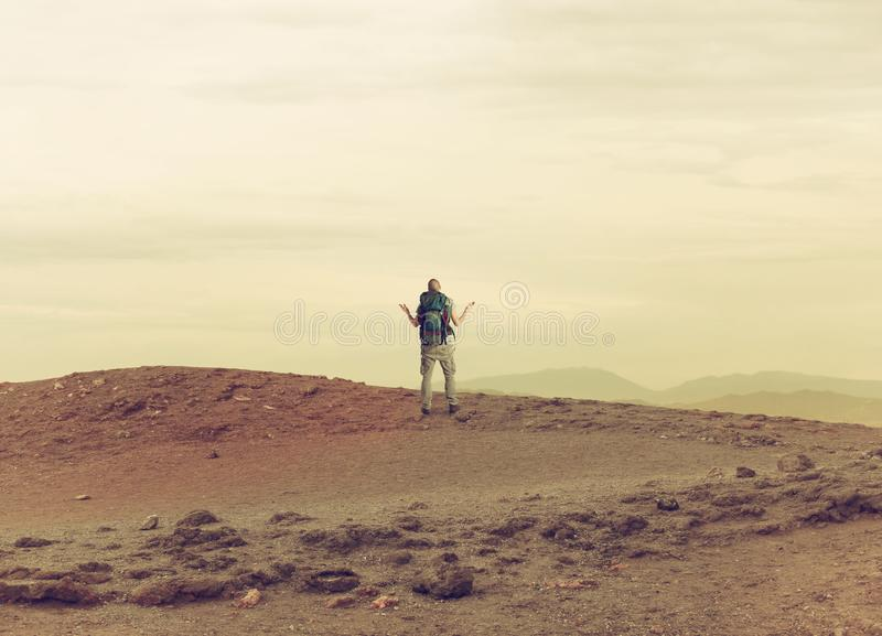 Uncertain explorer is lost in a desert. stock photo