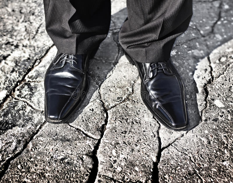Businessman legs standing on a cracked ground royalty free stock photography