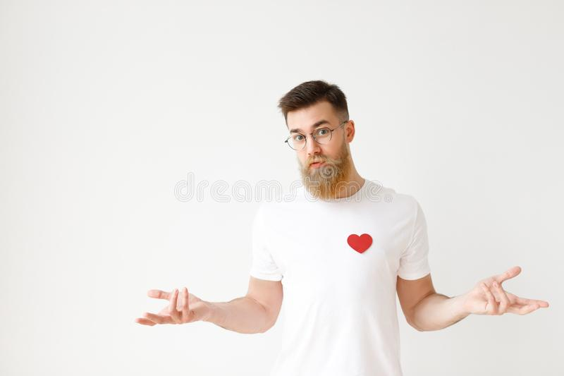 Uncertain hesitant bearded male in casual t shirt shruggs shoulders in bewilderment, tries to make decision about future. Life, over white studio background royalty free stock photography