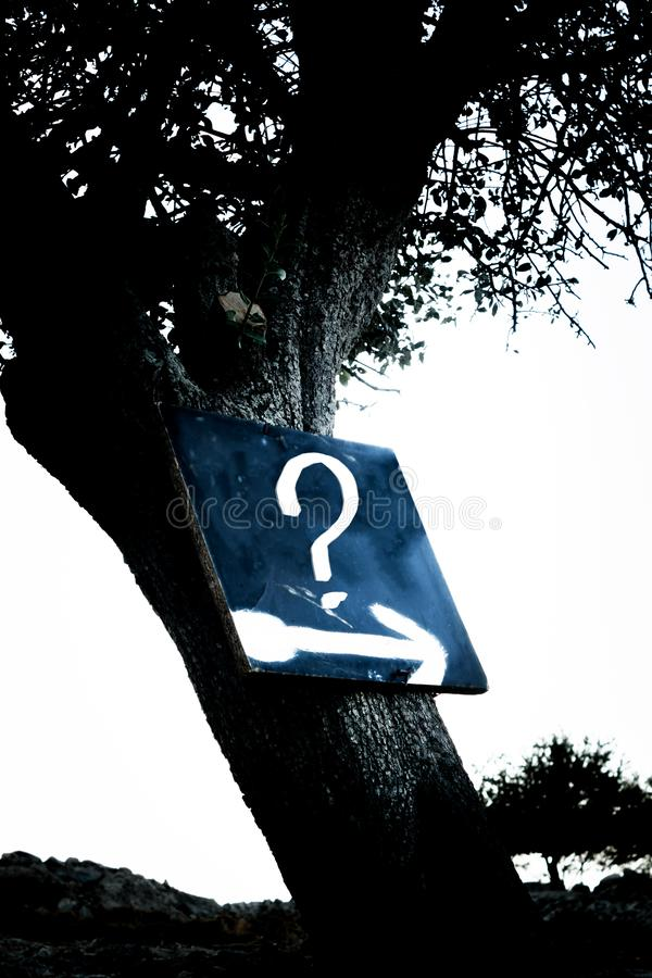 Uncertain, Unclear, Risky. Question Mark on Board. Uncertain, Unclear, Risky Expression in dark and gloomy woods. Question Mark and arrow sign on Board stock images