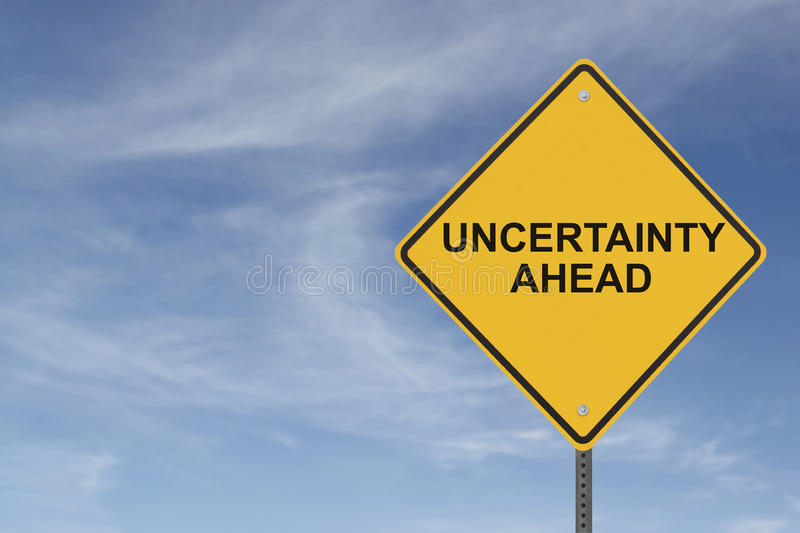 """Uncertainty Ahead. """"Uncertainty Ahead"""" sign with a background of blue sky with light cloudsrn stock photo"""