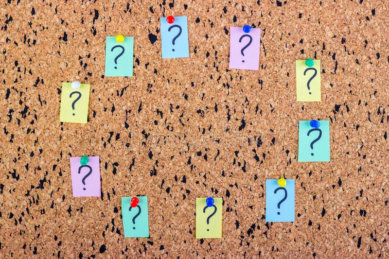 Uncertainty or doubt concept, question mark on a sticky note on cork bulletin board.  royalty free stock image