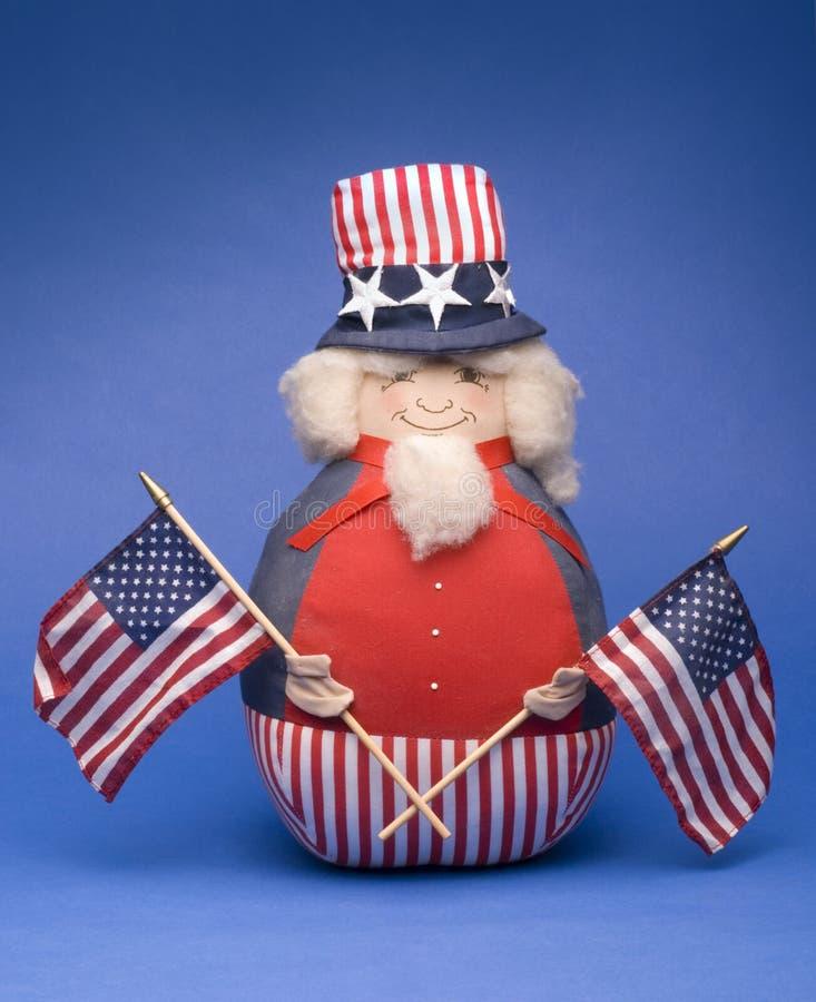 Uncle Sam stuffed toy. Antique uncle Sam stuffed toy shot on blue background stock photo