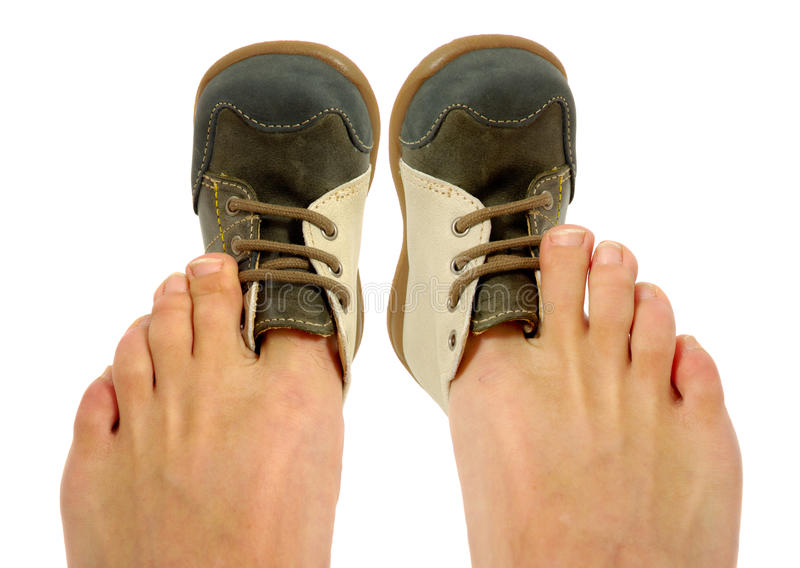 Uncomfortable shoes. An adolt is trying to fit a baby shoe royalty free stock photo