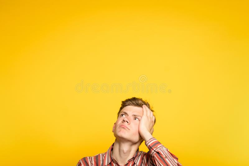 Puzzled bewildered confused man looking up stock photo
