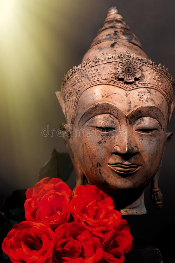 Unconditional love. Spiritual enlightenment. Traditional Buddha and red roses stock image