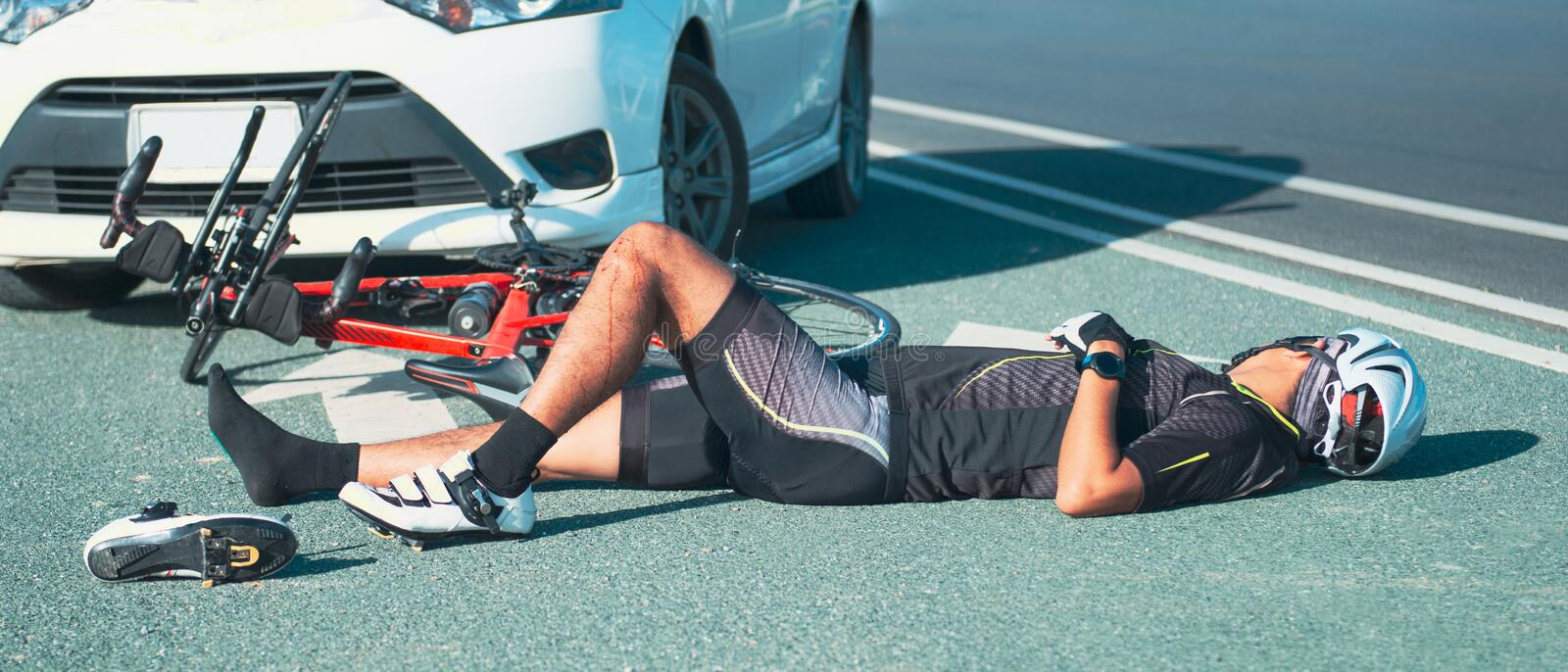 Unconscious male cyclist lying on road after road accident stock photography