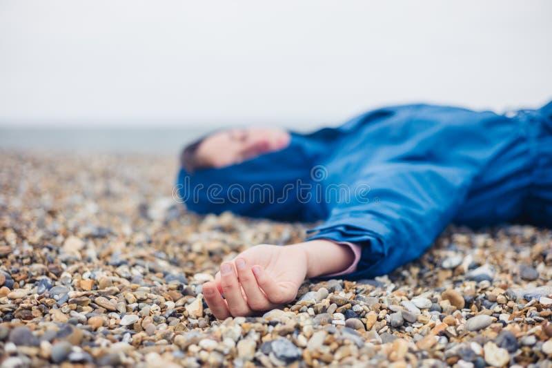 Unconscious woman on shingle beach. An unconscious woman is lying on a shingle beach stock image