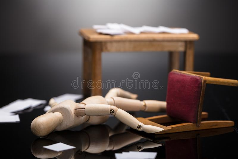 Unconscious Wooden Dummy Figure Lying On Floor. With Scattered Documents At Workplace stock images