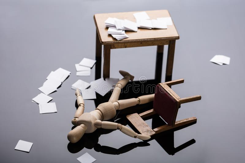 Unconscious Wooden Dummy Figure Lying On Floor. With Scattered Documents At Workplace stock photo
