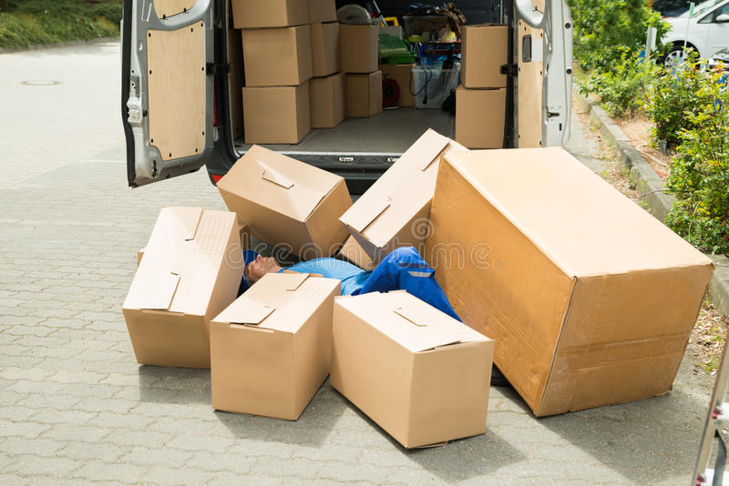 Unconscious Worker Lying On Street. Unconscious Male Worker Lying On Street Surrounded With Boxes stock photography