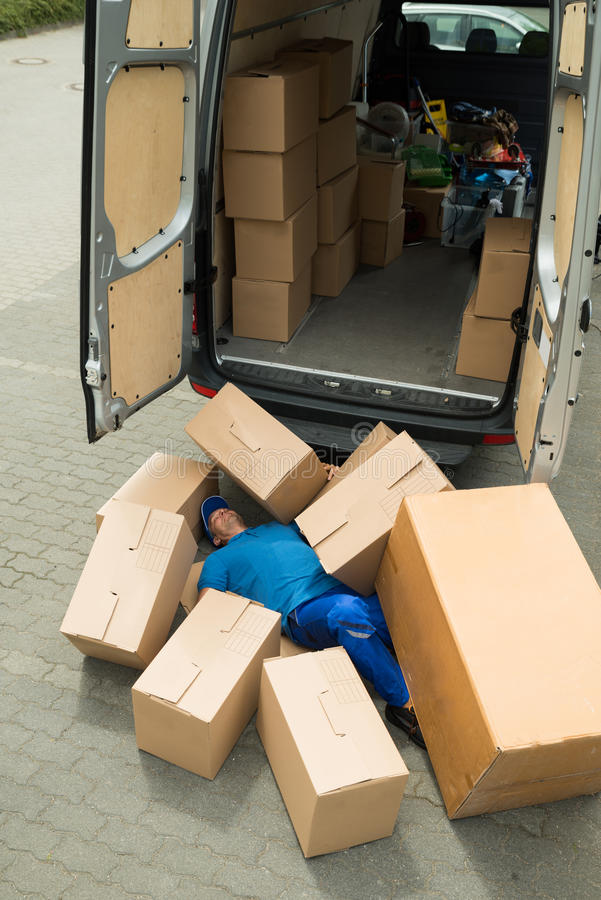 Unconscious Worker Lying On Street. Unconscious Male Worker Lying On Street Surrounded With Boxes royalty free stock image
