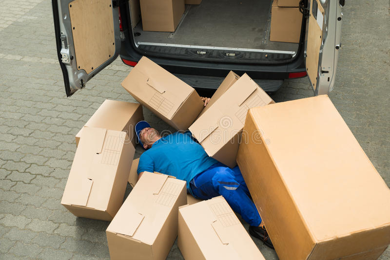 Unconscious Worker Lying On Street. Unconscious Male Worker Lying On Street Surrounded With Boxes stock image