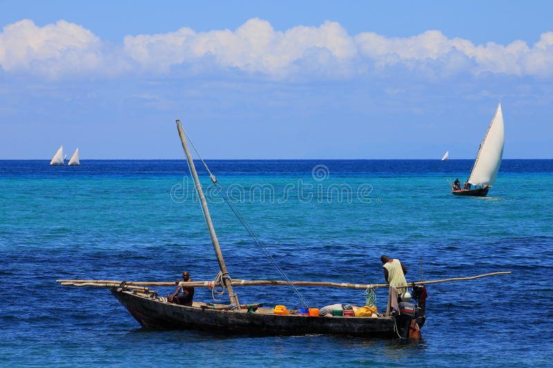 Unconventional workplaces. Nungwi Village, Zanzibar - fishermen depart on a dhow for a day of fishing in the Indian Ocean stock images