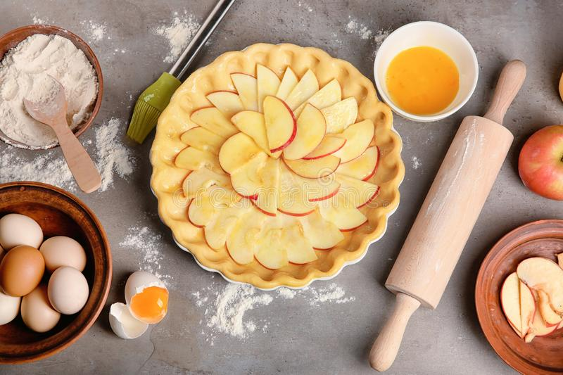 Uncooked apple pie with ingredients on table royalty free stock images