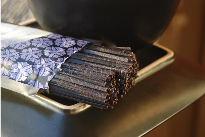 Uncooked black rice soba noodles on a plate stock photography