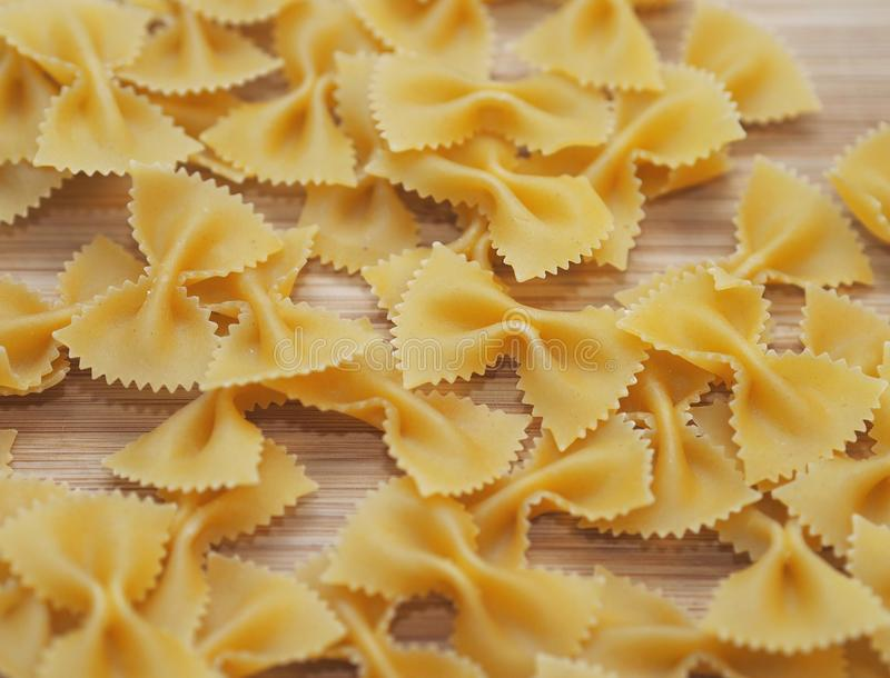 Uncooked bow-tie pasta (Farfalle). On a wooden board. The name of this pasta type is derived from the Italian word farfalla (butterfly royalty free stock photography
