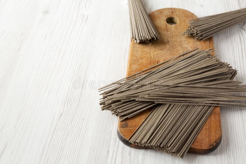 Uncooked buckwheat soba noodles on rustic wooden board over white wooden surface, side view. Copy space royalty free stock images