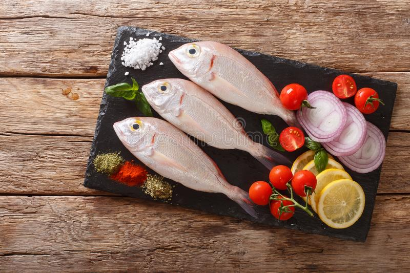 Uncooked dorado or gilt-head sea bream fish with spices, tomato, onion and lemon close up on a slate board. horizontal top view. Uncooked dorado or gilt-head sea royalty free stock photo
