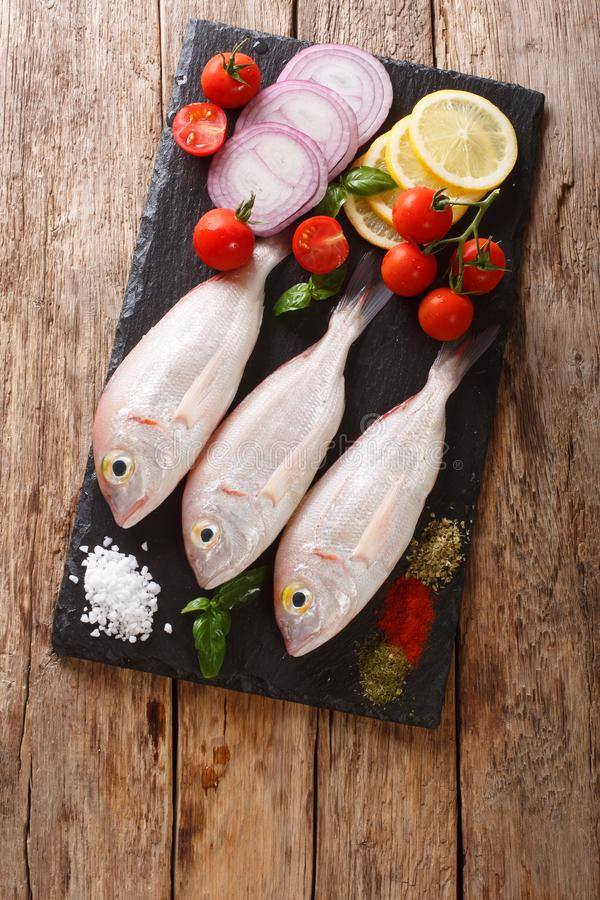 Uncooked dorado or gilt-head sea bream fish with spices, tomato, onion and lemon close up on a slate board. Vertical top view. Uncooked dorado or gilt-head sea stock photos