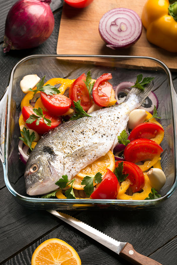 Uncooked dorado or sea bass. Fish with vegetables, herbs and spices royalty free stock photos