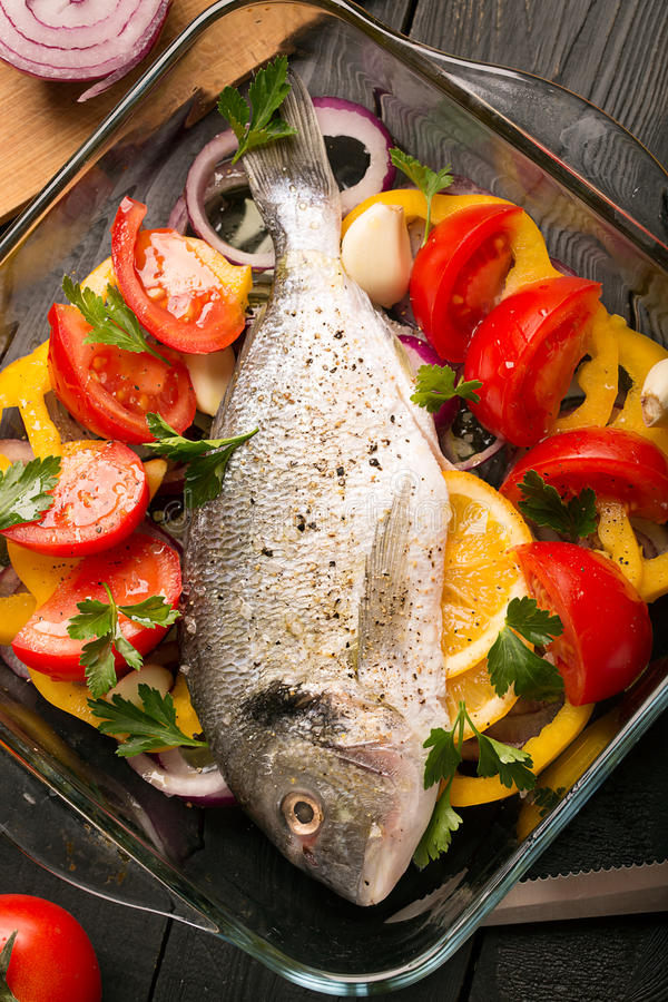 Uncooked dorado or sea bass. Fish with vegetables, herbs and spices stock photos