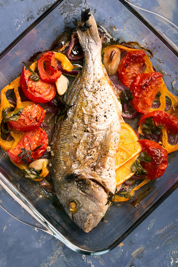 Uncooked dorado or sea bass. Fish with vegetables, herbs and spices stock photo