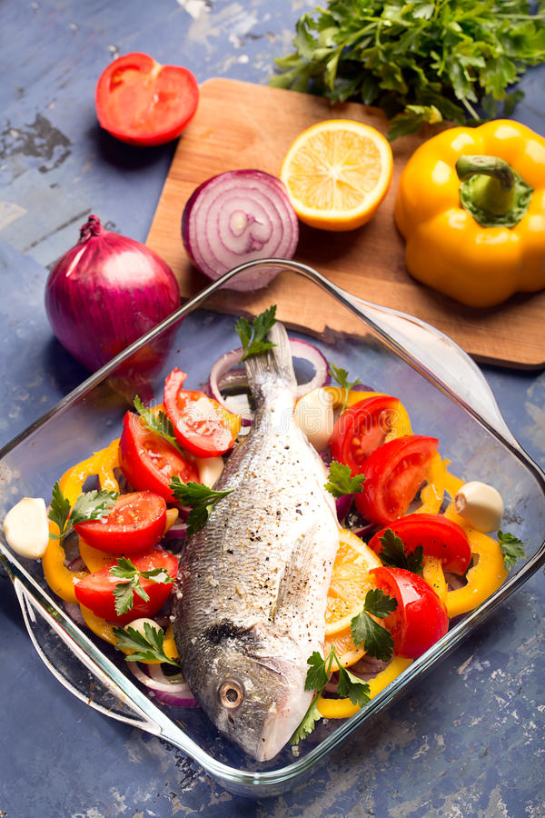 Uncooked dorado or sea bass. Fish with vegetables, herbs and spices stock image
