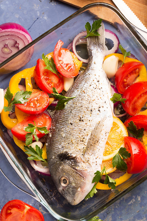 Uncooked dorado or sea bass. Fish with vegetables, herbs and spices royalty free stock image
