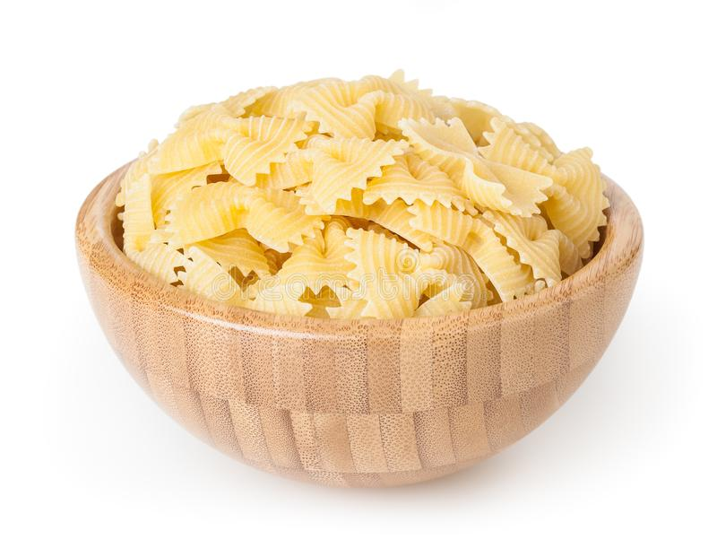 Uncooked dried bow tie pasta in wooden bowl isolated on white background stock photography