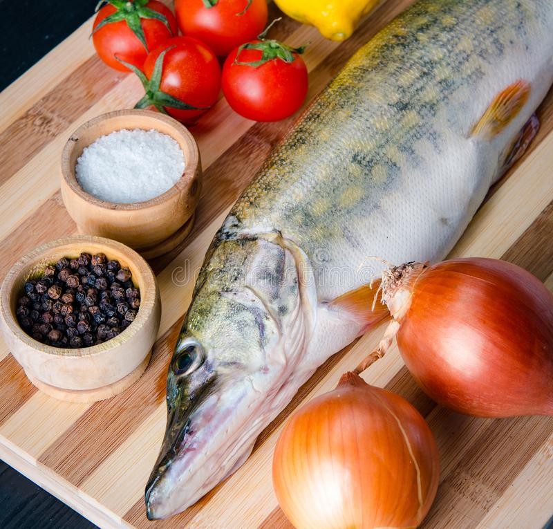 Uncooked fish on cutting board in meal preparation concept stock photo
