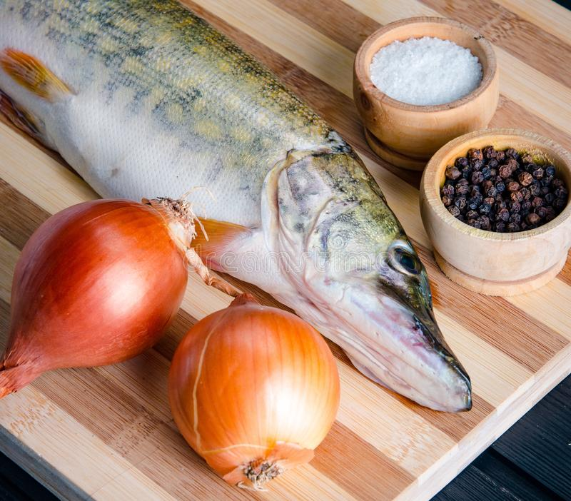 Uncooked fish on cutting board in meal preparation concept royalty free stock images