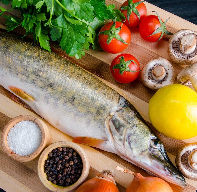Uncooked fish on cutting board in meal preparation concept royalty free stock photos