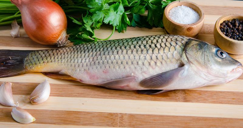 The uncooked fish on cutting board in meal preparation concept stock image