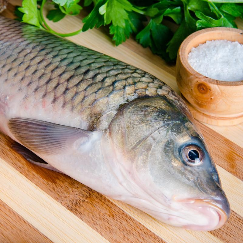 Uncooked fish on cutting board in meal preparation concept stock images